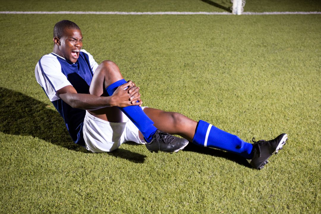 Young male soccer player shouting in agony with knee pain on playing field Free Stock Images from PikWizard