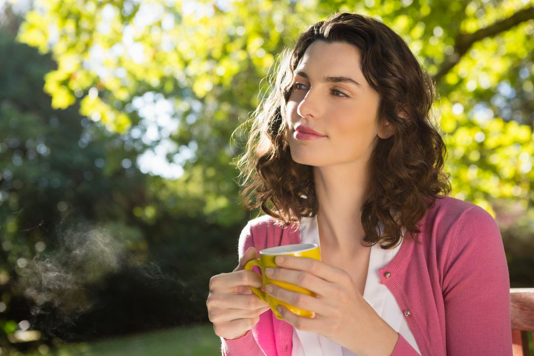 Thoughtful woman holding a cup of coffee in garden