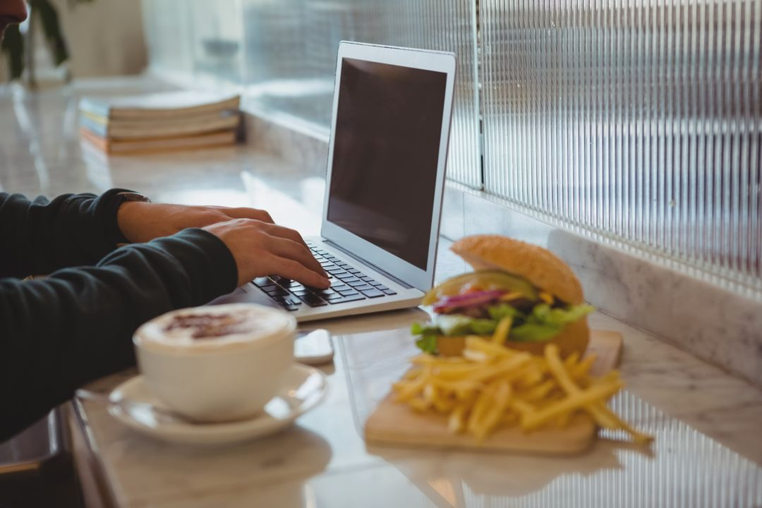 Cropped hands of man using laptop by coffee cup and French fries at counter in cafe Free Stock Images from PikWizard