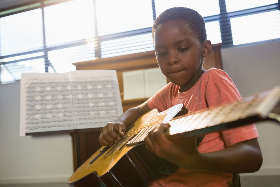 Boy playing guitar in class at music school