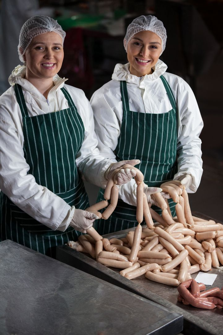 Portrait of female butchers processing sausages at meat factory Free Stock Images from PikWizard