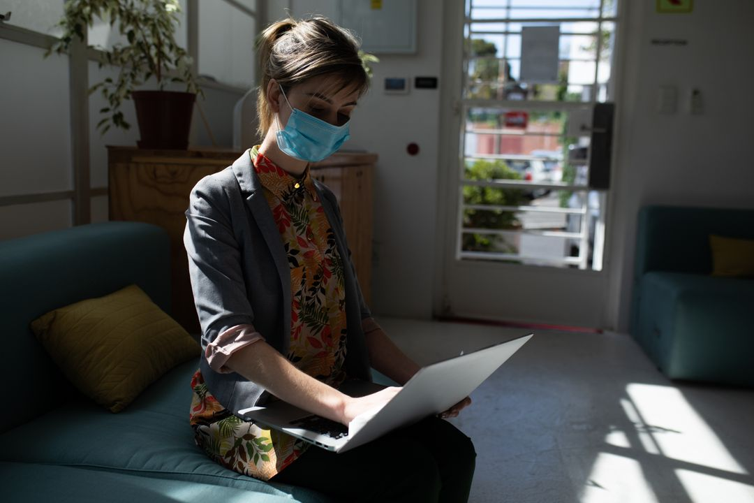 A caucasian woman sitting on the couch at an office wearing a facemask. She is typing on her laptop. Free Stock Images from PikWizard
