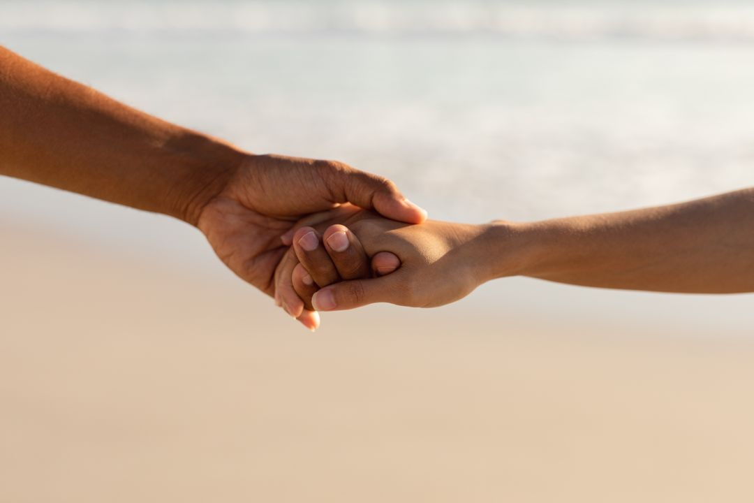 Close-up of couple holding hands of each other on the beach