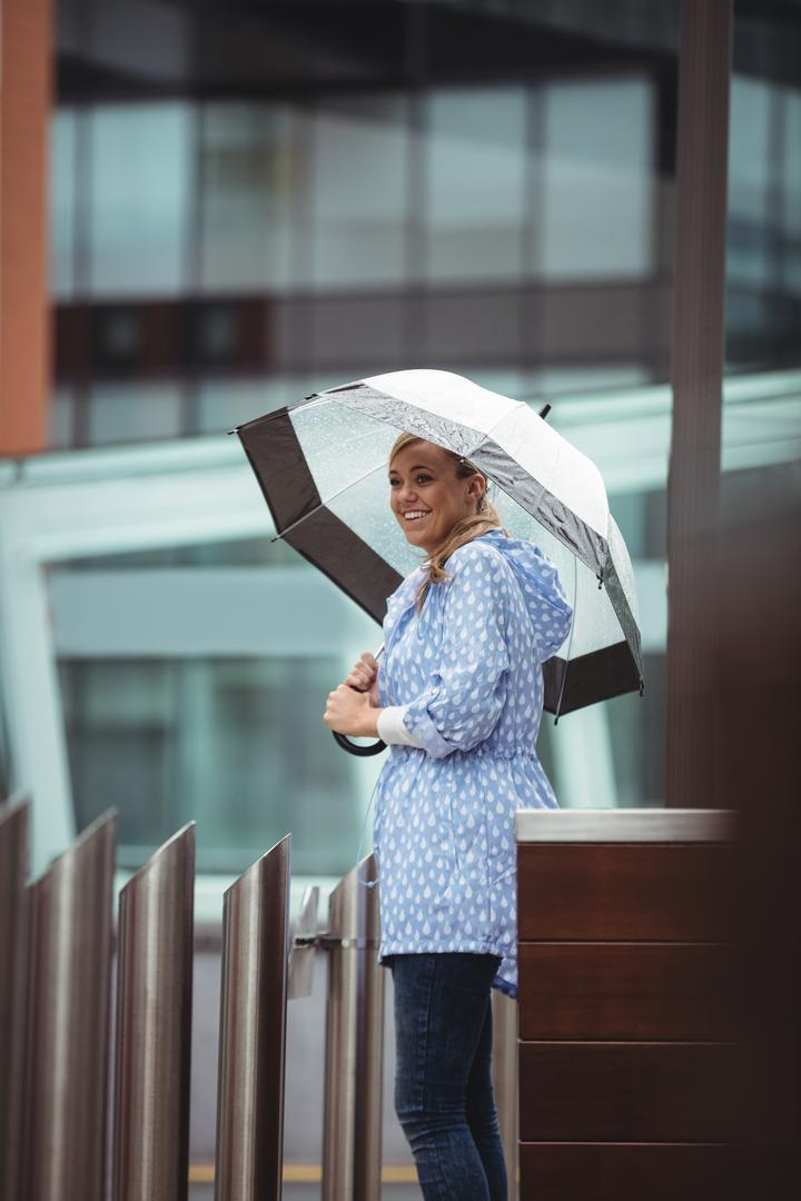 Beautiful woman holding umbrella and standing on street during rainy season