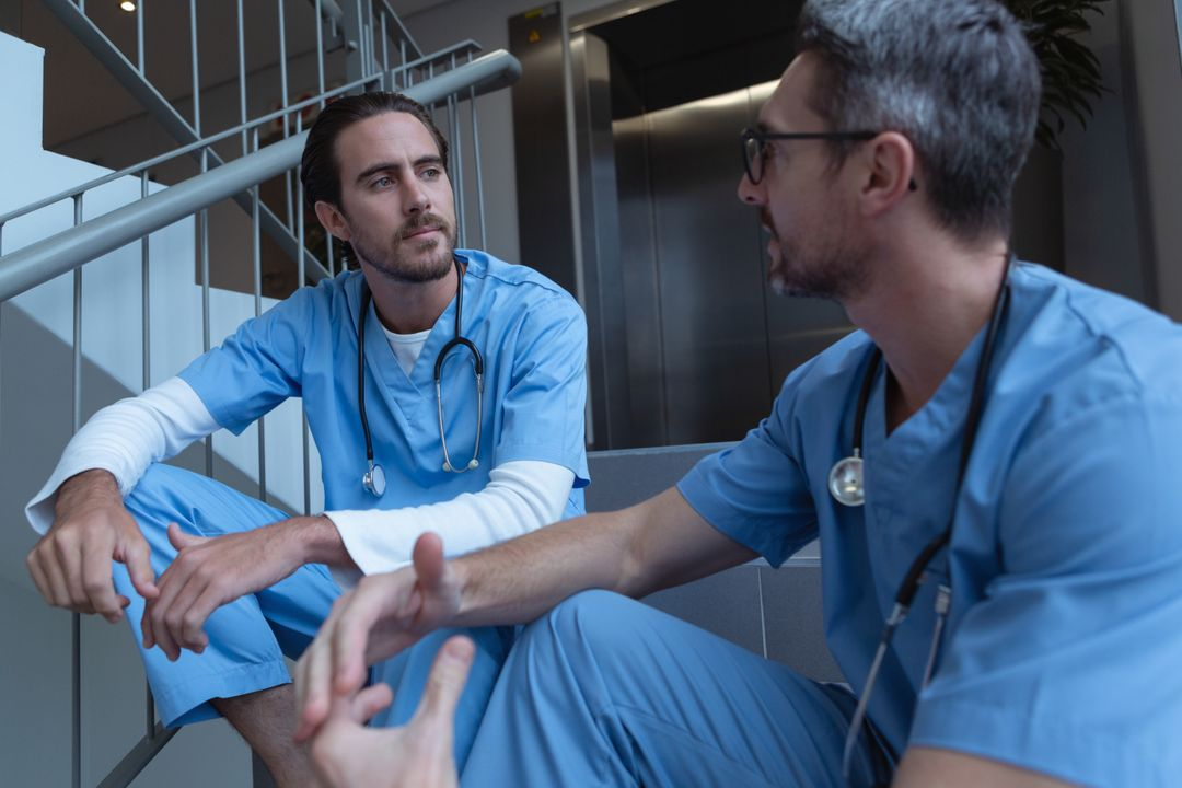 Front view of male surgeons talking with each other while sitting on stairs at hospital Free Stock Images from PikWizard