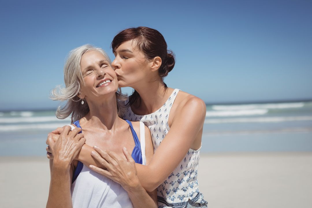 Young woman kissing her mother at beach during sunny day