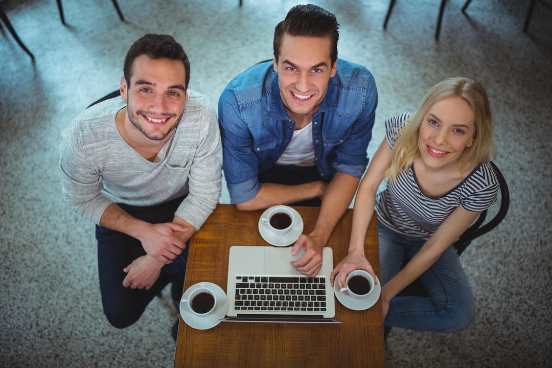 Portrait of smiling friends using laptop while having coffee in café