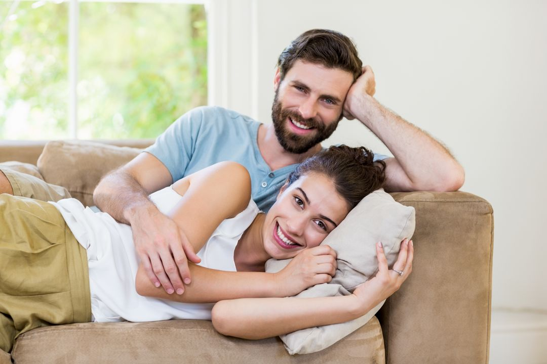 Portrait of young couple relaxing on sofa at home Free Stock Images from PikWizard
