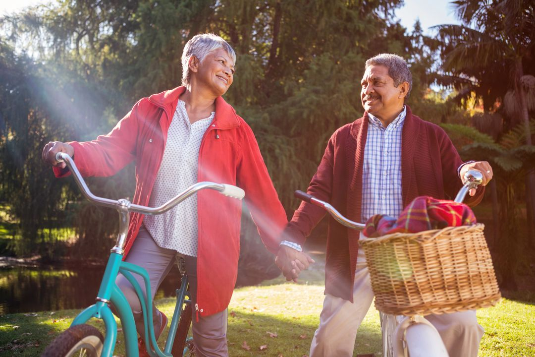 Happy mature couple with bicycle at park during autumn Free Stock Images from PikWizard