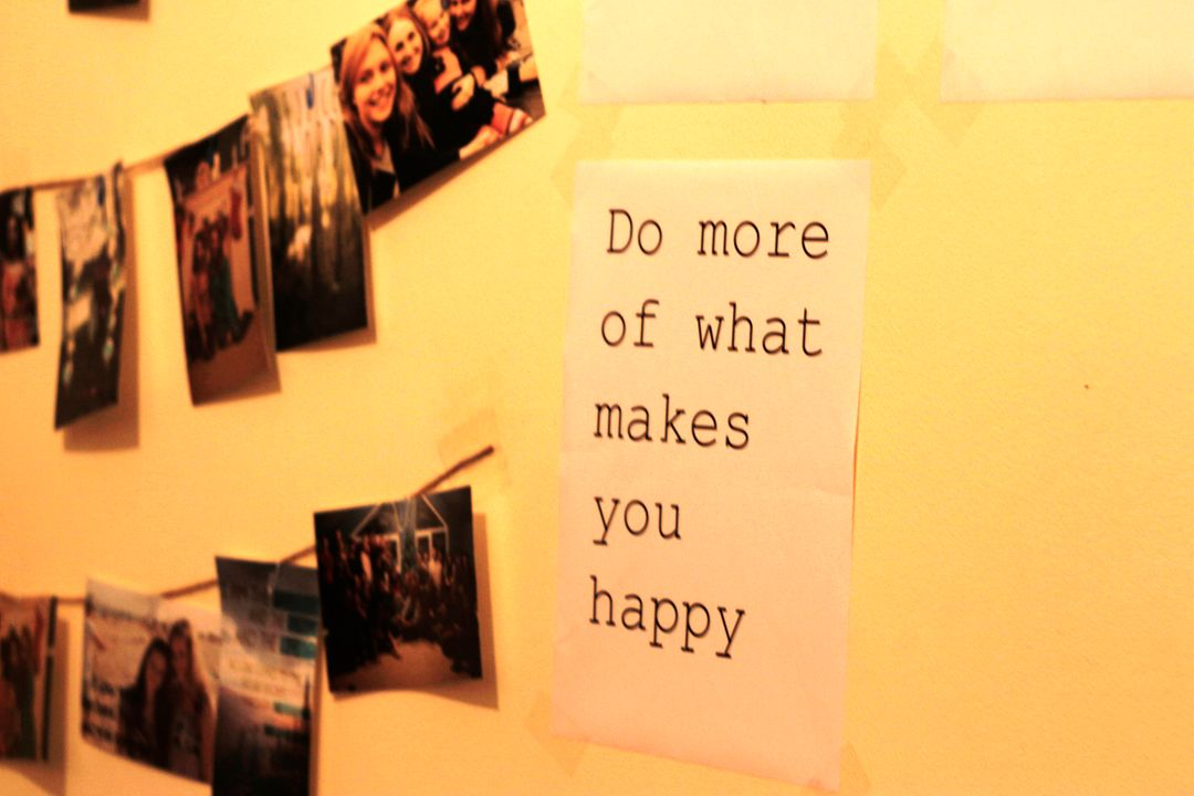 image of a printed quote with accompaning images of a collection of friends, on a persons wall