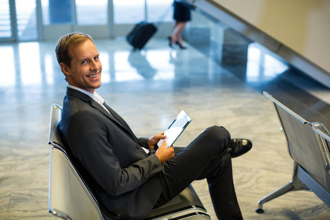 Portrait of businessman using digital tablet in the waiting area at the airport terminal Free Stock Images from PikWizard