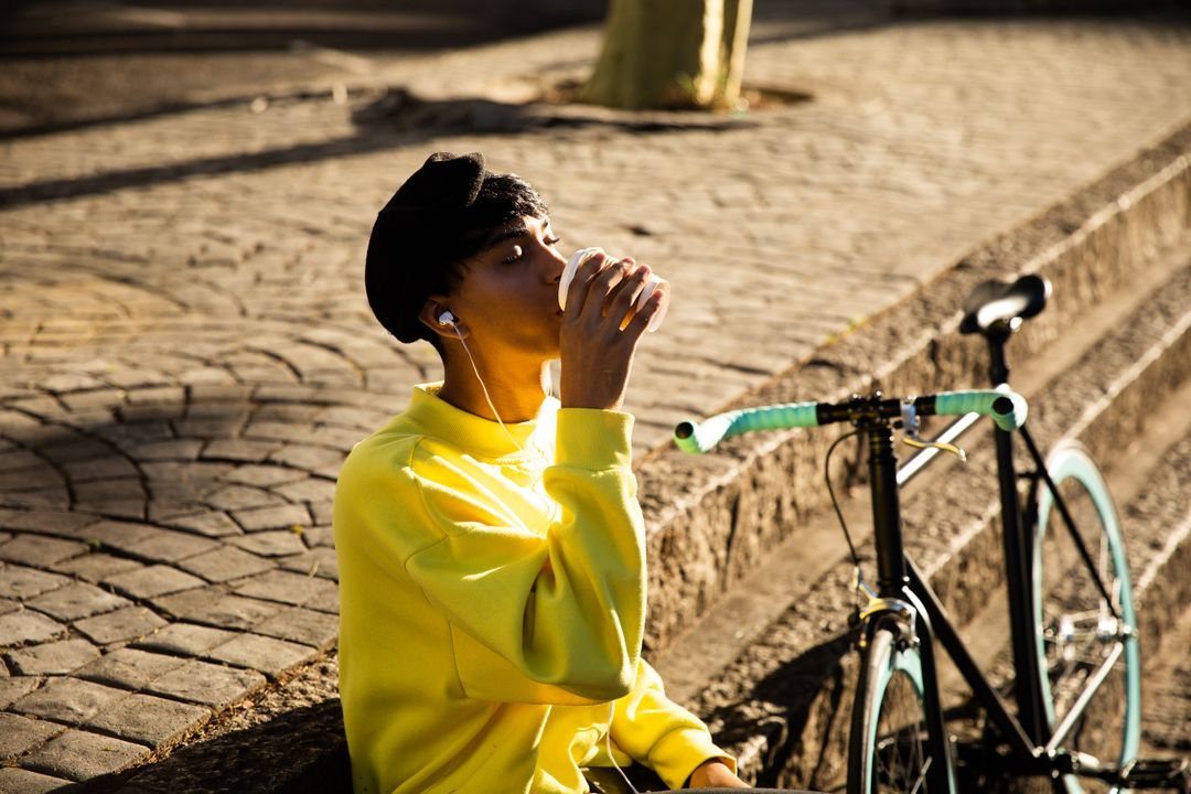 Side view of a fashionable mixed race transgender in the street, leaning on a wall, drinking coffee, listening to music on earphones, with a bike standing by him Free Stock Images from PikWizard