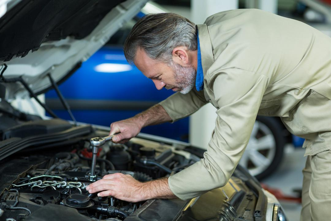Mechanic servicing a car engine in repair garage