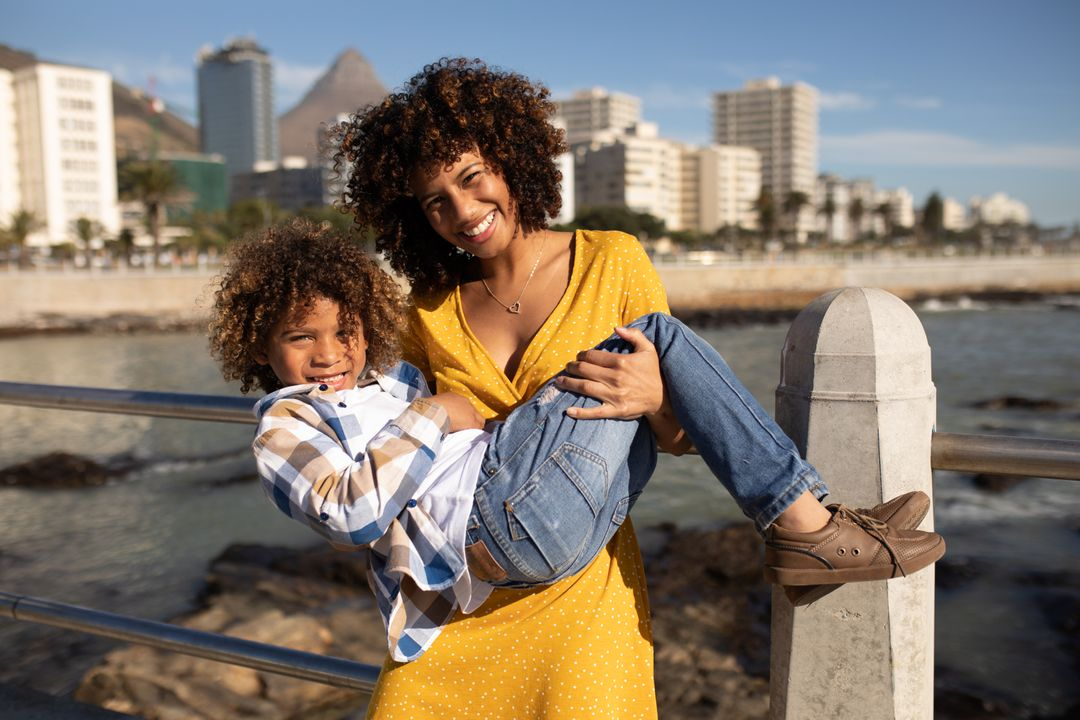 Portrait of a mixed race woman wearing a yellow dress and her son enjoying time together by the sea, standing on a premanade by the sea on a sunny day, the woman holding her son in her arms and both smiling to camera Free Stock Images from PikWizard