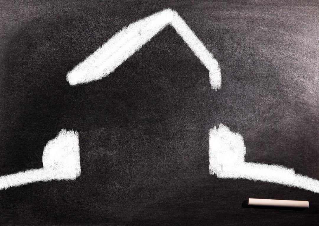 Close up of white outlined home icon on blackboard