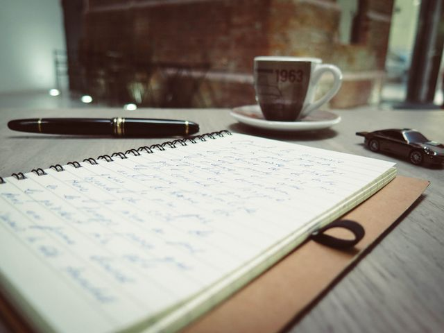 Pen, notepad and coffee on a table