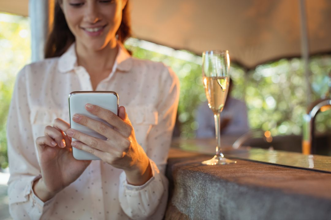 Smiling woman using mobile phone while having a glass of champagne in restaurant Free Stock Images from PikWizard