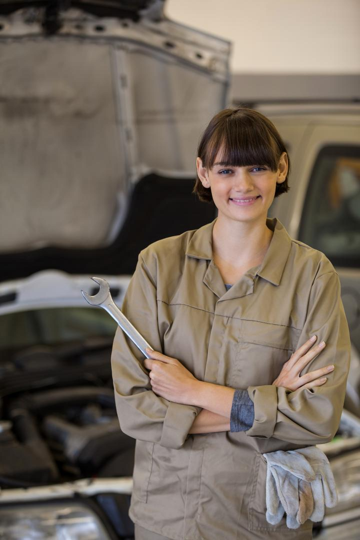 Portrait of female mechanic with arms crossed and spanner at the repair garage