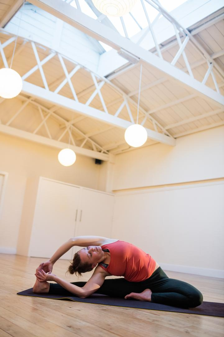 Woman performing yoga on exercise mat in fitness studio