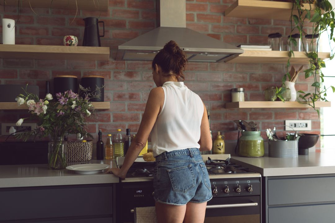 Rear view of woman preparing food in kitchen at comfortable home