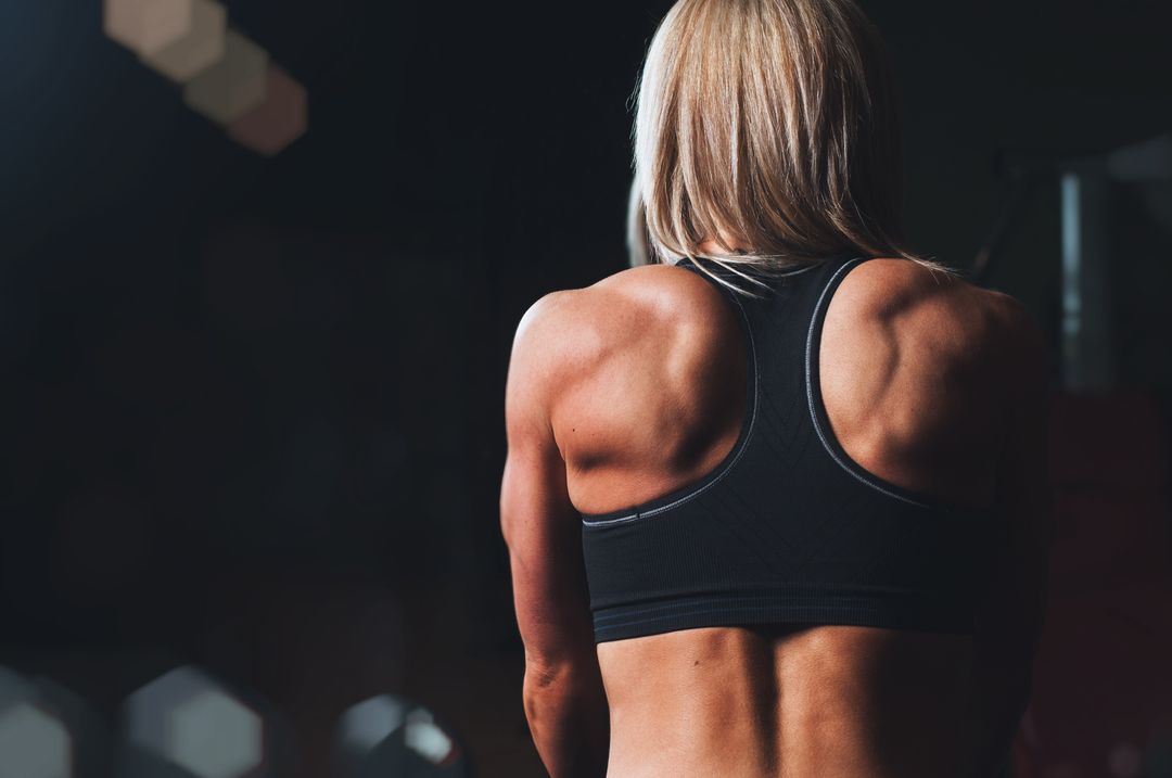 Woman back flexing at a gym