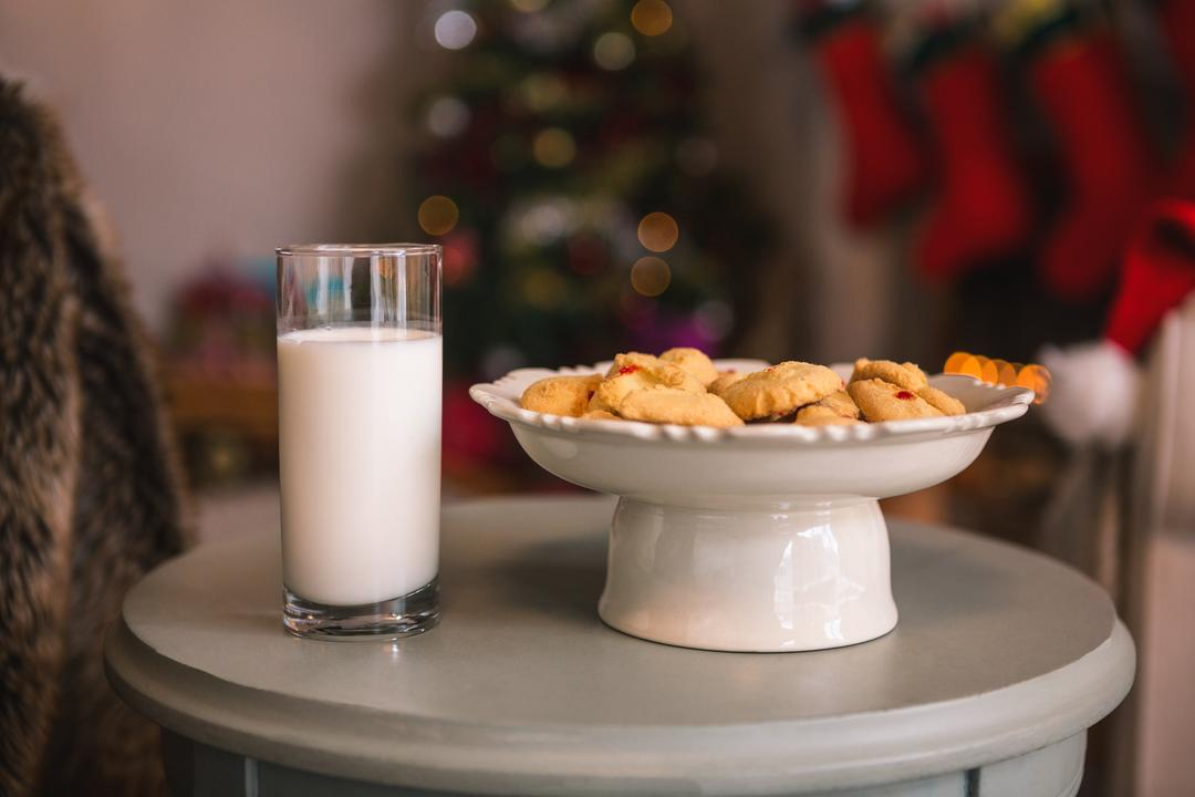 Christmas cookies on plate with a glass of milk on wooden table during christmas time Free Stock Images from PikWizard