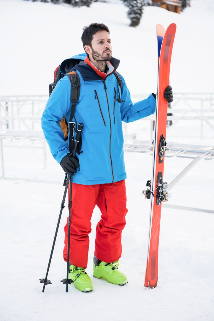 Skier standing with ski on snow covered mountains Free Stock Images from PikWizard