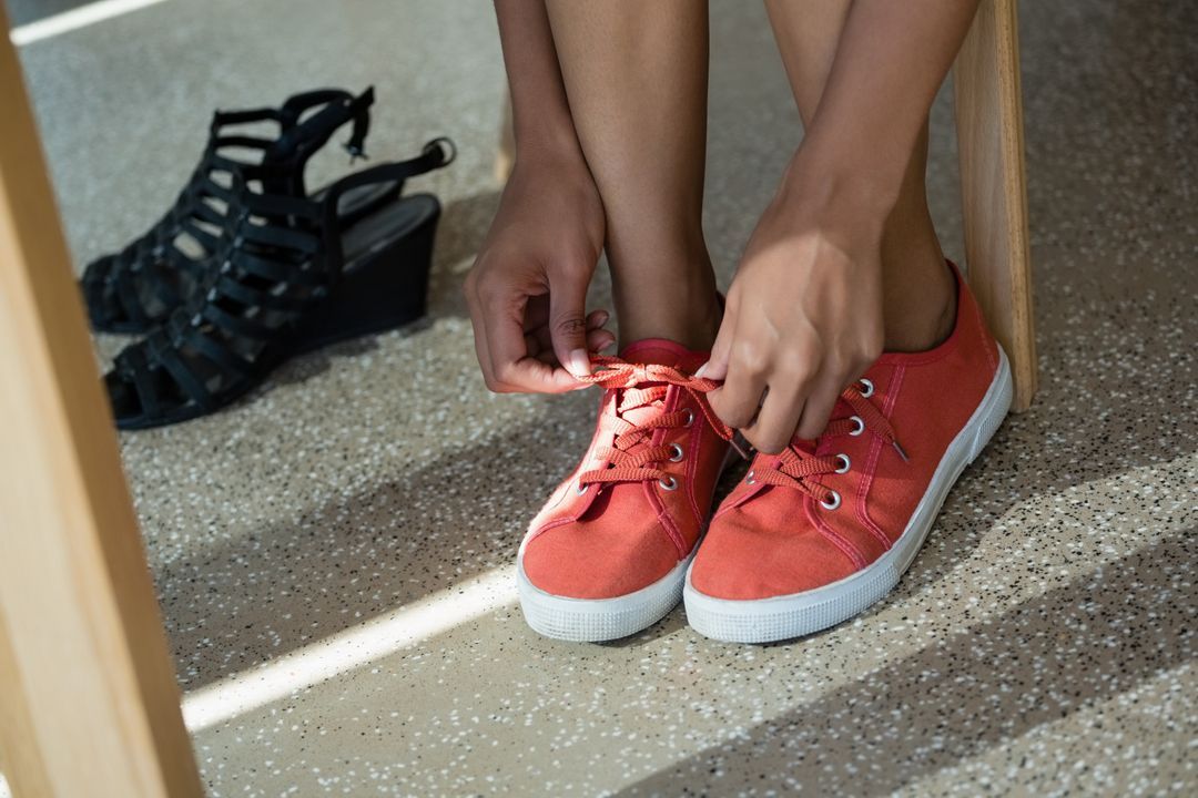 Low section of woman wearing canvas shoes in office Free Stock Images from PikWizard