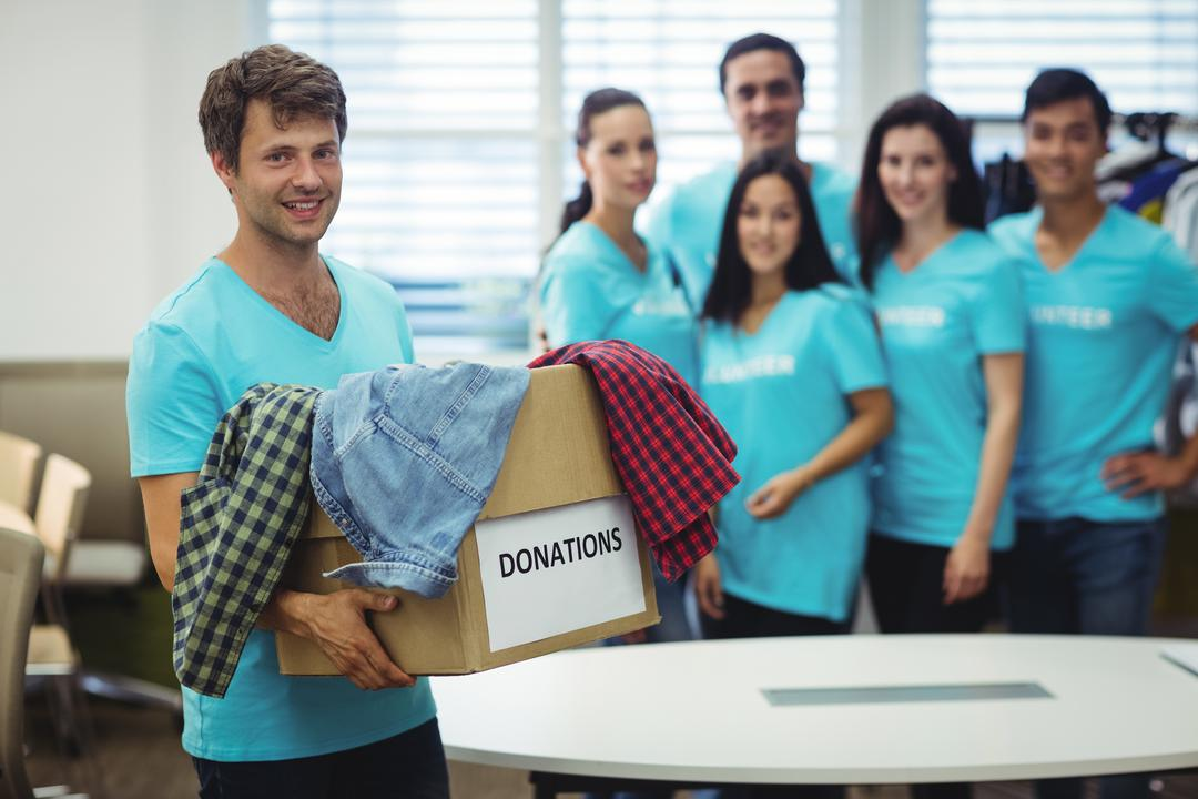 Portrait of volunteer holding clothes in donation box at workshop