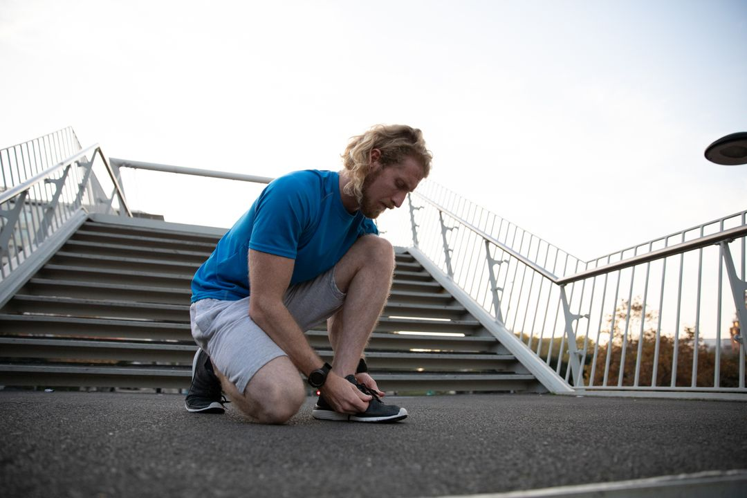 Low angle front view of a fit Caucasian man with long blonde hair wearing sportswear exercising outdoors in the city on a sunny day with blue sky, kneeling and tying his shoe. Free Stock Images from PikWizard