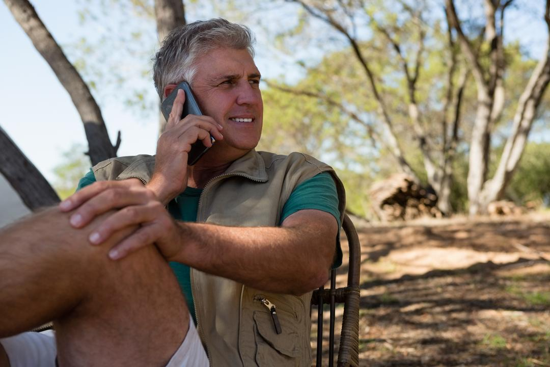 Mature man looking away while talking on phone at campsite