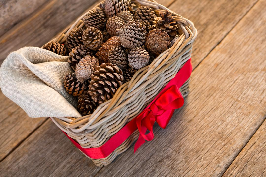 Pine cones in wicker basket tied with red ribbon on wooden plank during christmas time Free Stock Images from PikWizard