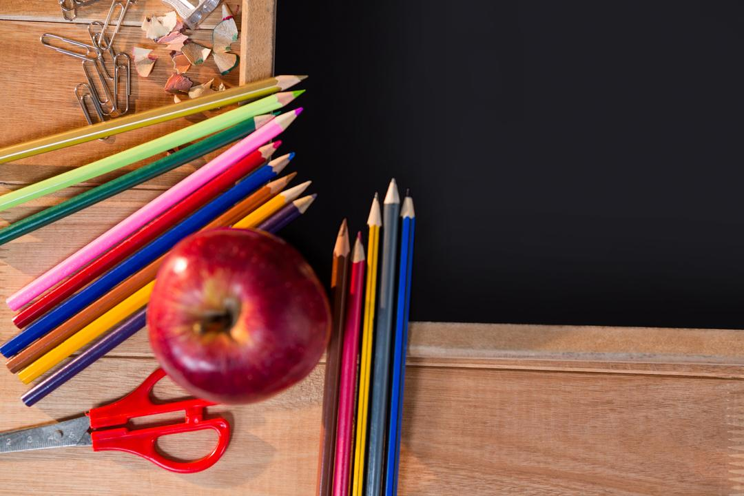 Close-up of chalkboard with colored pencil and apple on a table