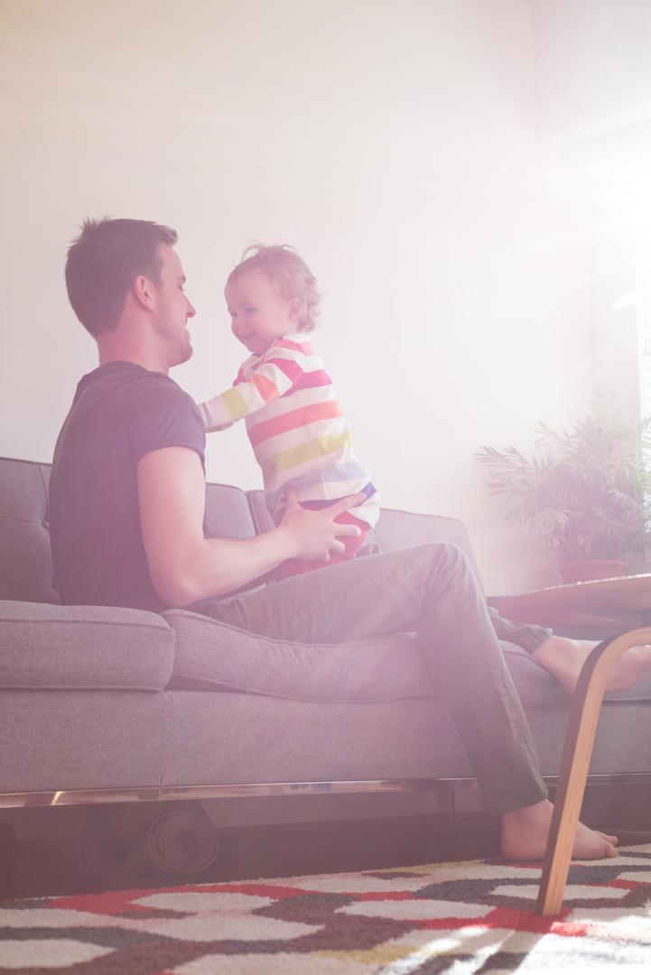 Side view of playful father with daughter on sofa at home