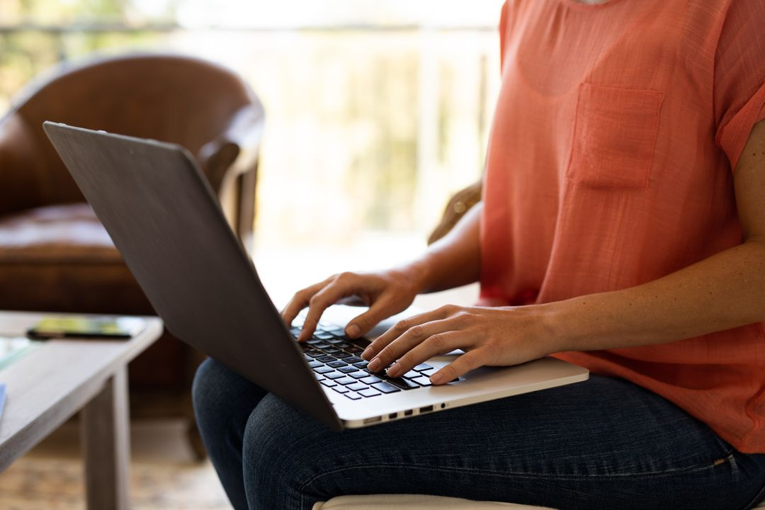 A caucasian woman sitting on a couch in their living room at home while typing on her laptop. Her phone can be seen on the table in the background. Free Stock Images from PikWizard