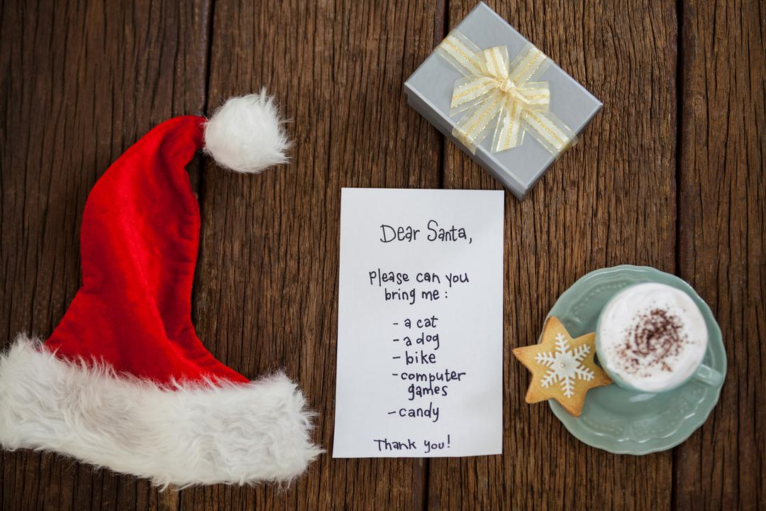 Letter for Santa, gift, coffee and cookie on wooden board
