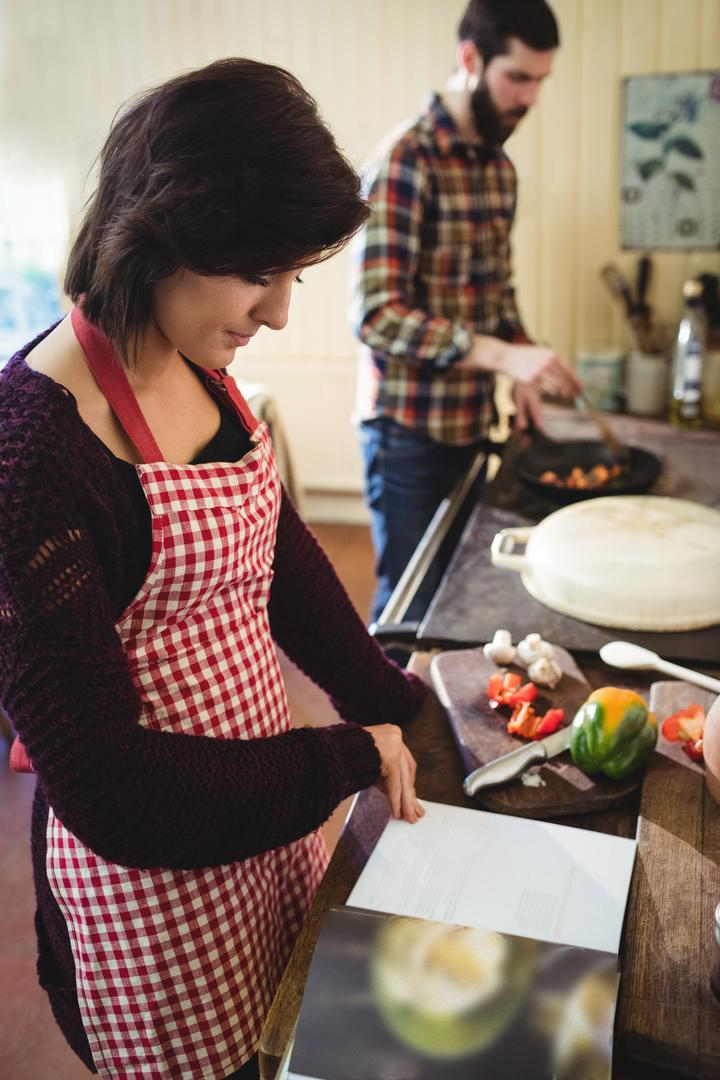 Woman reading a recipe book in kitchen at home