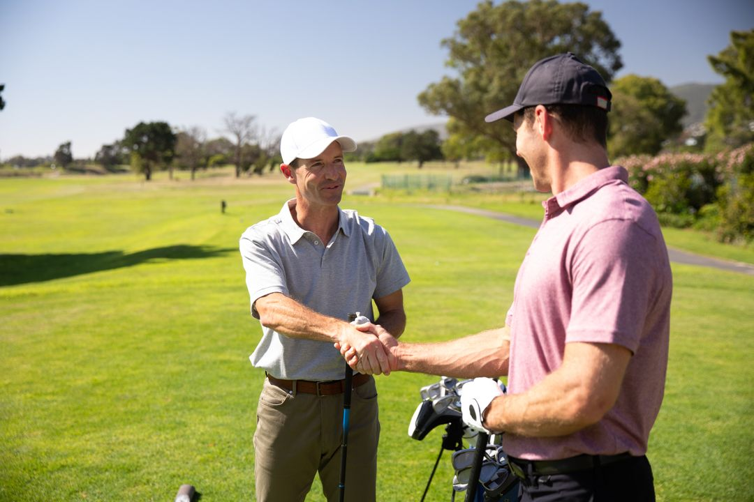 Two Caucasian male golfers practicing on a golf course on a sunny day wearing caps and golf clothes, shaking hands holding golf clubs. Hobby healthy lifestyle leisure. Free Stock Images from PikWizard