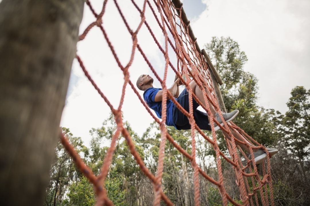 Fit man climbing a net during obstacle course in boot camp Free Stock Images from PikWizard