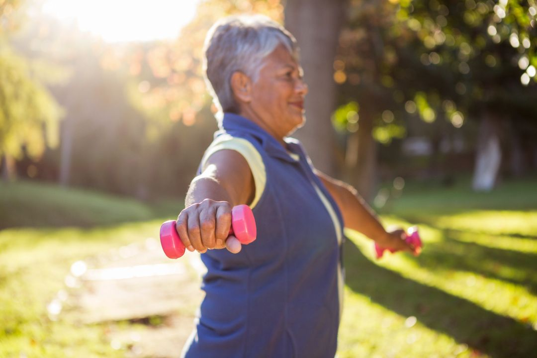 Side view of mature woman exercising with dumbbell at park on sunny day