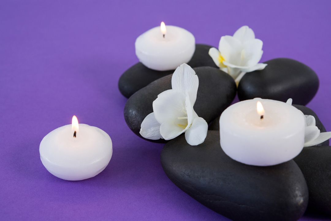 White flowers, candles on zen stone on purple background Free Stock Images from PikWizard