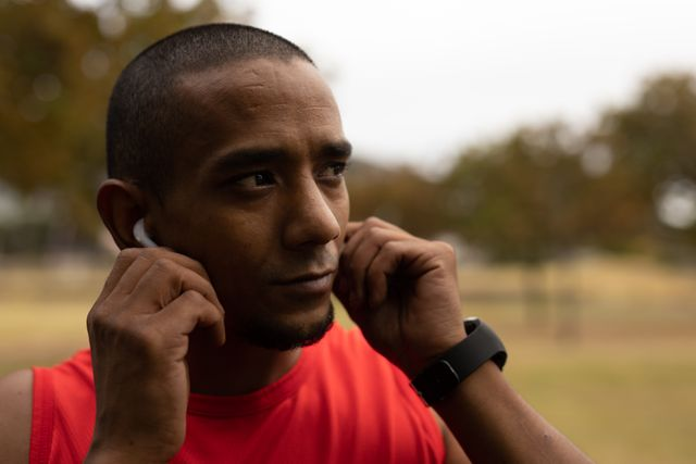 Mixed race man wearing sportswear and smartwatch, listening to music on wireless earphones, taking a break from running workout. Fitness outdoor healthy lifestyle.