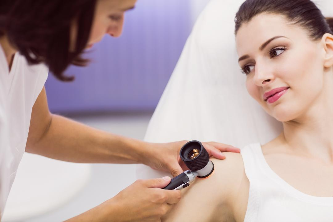 Dermatologist examining skin of patient with dermatoscope in clinic Free Stock Images from PikWizard