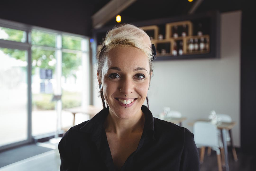 Portrait of smiling waitress standing in cafe