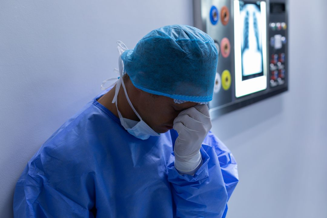 Tensed male surgeon with hand over face sitting in operation theater at hospital