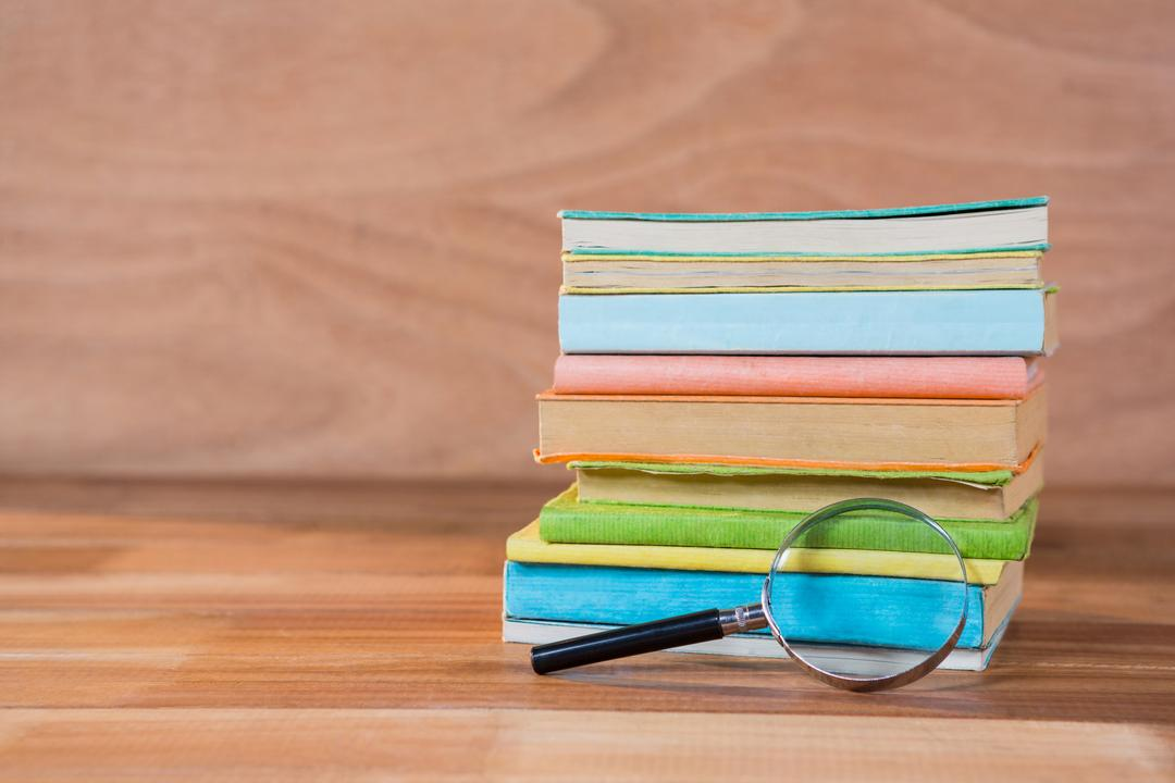 Magnifying glass with stack of books on a wooden table Free Stock Images from PikWizard