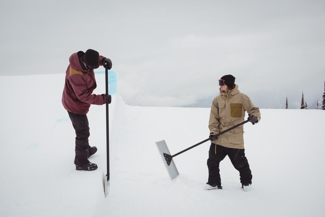 Two men cleaning snow in ski resort during winter