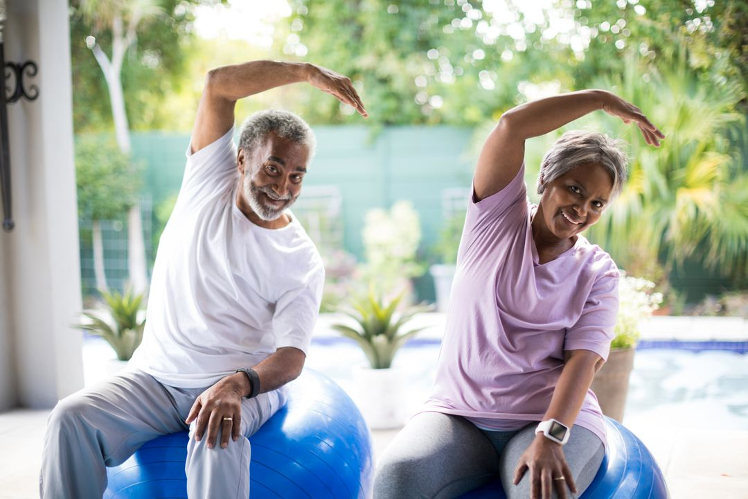 Portrait of senior couple exercising while sitting on fitness ball in yard