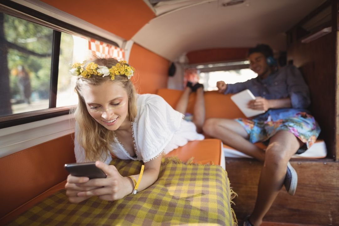 Woman smiling with phone inside colourful camper van