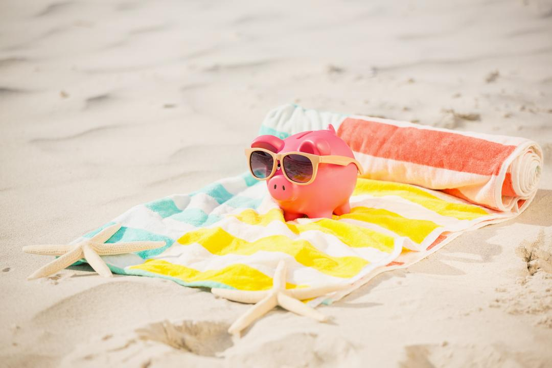 Image of a Piggy Bank with Sunglasses at the Beach